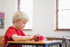 Cute pupil opening lunchbox at desk in classroom Stock Images