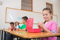 Cute pupil opening lunchbox at desk in classroom Royalty Free Stock Image