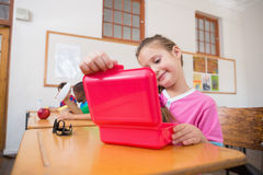 Cute pupil opening lunchbox at desk in classroom Stock Image