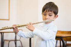 Cute pupil playing flute in classroom Royalty Free Stock Images