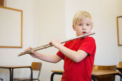Cute pupil playing flute in classroom Royalty Free Stock Photos