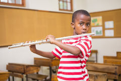 Cute pupil playing flute in classroom Stock Photos
