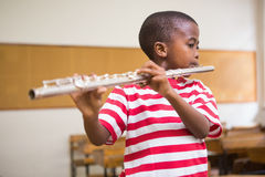 Cute pupil playing flute in classroom Stock Photo