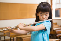 Cute pupil playing flute in classroom Royalty Free Stock Image