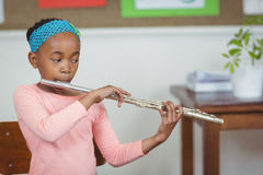 Cute pupil playing flute in a classroom Stock Image