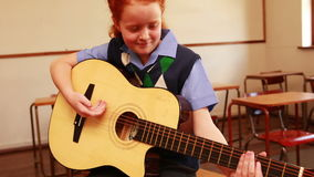 Cute pupil playing guitar in classroom. At the elementary school stock video footage