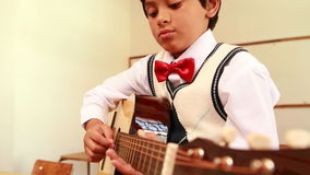 Cute pupil playing guitar in classroom. At the elementary school stock footage