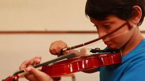 Cute pupil playing violin in classroom. At the elementary school stock footage