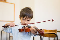 Cute pupil playing violin in classroom Stock Image