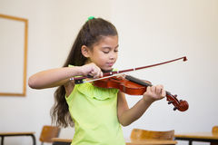 Cute pupil playing violin in classroom Royalty Free Stock Photography