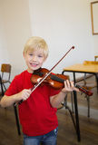 Cute pupil playing violin in classroom Royalty Free Stock Image