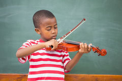Cute pupil playing violin in classroom Royalty Free Stock Images