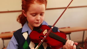 Cute pupil playing violin in classroom. At the elementary school stock video
