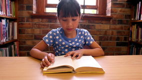Cute pupil reading a book at the library stock video