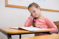 Cute pupil reading at her desk Stock Photo