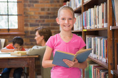 Cute pupil reading in library Royalty Free Stock Photos