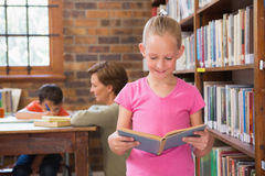 Cute pupil reading in library Royalty Free Stock Images