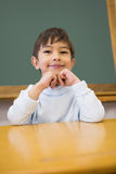 Cute pupil sitting at desk in classroom Stock Image