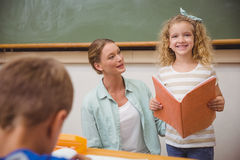 Cute pupil smiling at camera during class presentation Royalty Free Stock Photo