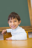 Cute pupil smiling at camera in classroom Stock Photography