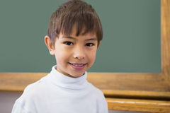 Cute pupil smiling at camera in classroom Stock Photos