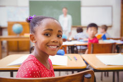 Cute pupil smiling at camera in classroom Royalty Free Stock Photo