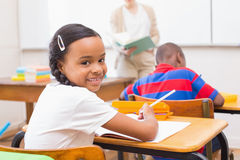 Cute pupil smiling at camera in classroom Stock Image