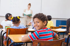 Cute pupil smiling at camera in classroom Stock Photo
