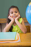 Cute pupil smiling at camera classroom with globe Stock Photography