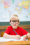 Cute pupil smiling at camera in classroom at his desk Royalty Free Stock Photography