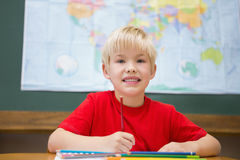 Cute pupil smiling at camera in classroom at his desk Stock Image