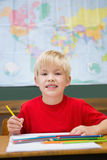 Cute pupil smiling at camera in classroom at his desk Stock Photography