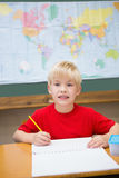 Cute pupil smiling at camera in classroom at his desk Stock Photos