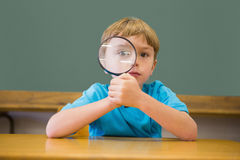 Cute pupil smiling at camera in classroom holding magnifying glass Stock Photography