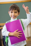 Cute pupil smiling at camera in classroom holding notepad Stock Images