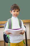 Cute pupil smiling at camera in classroom holding notepad Royalty Free Stock Photos