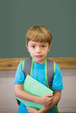 Cute pupil smiling at camera in classroom holding notepad Stock Photos