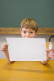 Cute pupil smiling at camera in classroom showing page Royalty Free Stock Photos