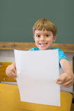 Cute pupil smiling at camera in classroom showing page Stock Photo