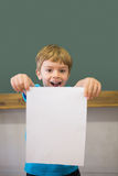 Cute pupil smiling at camera in classroom showing page Royalty Free Stock Photo