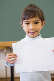 Cute pupil smiling at camera in classroom showing page Royalty Free Stock Image