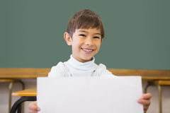 Cute pupil smiling at camera in classroom showing page Royalty Free Stock Images