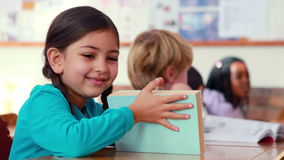 Cute pupil smiling at camera at her desk in classroom. In elementary school stock video