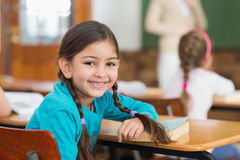 Cute pupil smiling at camera at her desk in classroom Stock Photos