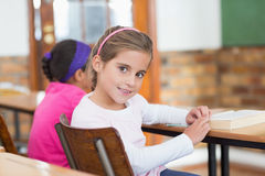 Cute pupil smiling at camera at her desk in classroom Stock Image