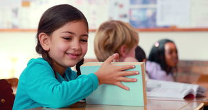 Cute pupil smiling at camera at her desk in classroom. In elementary school stock footage