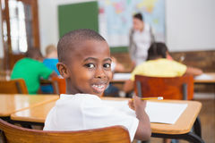 Cute pupil smiling at camera at his desk in classroom Stock Photography