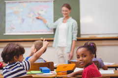 Cute pupil smiling at camera at his desk in classroom Royalty Free Stock Images