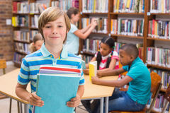 Cute pupil smiling at camera in library Royalty Free Stock Image