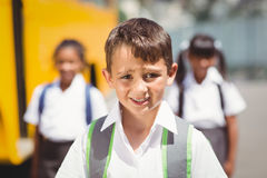 Cute pupil smiling at camera by the school bus Stock Photography